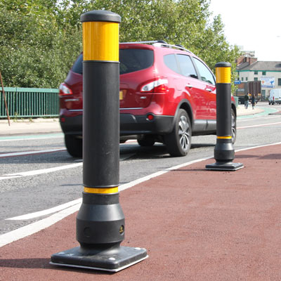 Black Bolt-Down Neopolitan 150 bollards with amber retroreflective banding